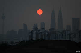 A general view shows Malaysia's landmark Petronas Twin Towers (2nd R) and Kuala Lumpur Tower (L) as a layer of haze covers the city during sunset in Kuala Lumpur on March 30, 2016.