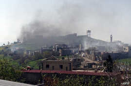 A picture taken with a smart phone shows smoke rising in village of al-Hosn in the Homs region, about 200 kms northwest of the capital Damascus, on March 20, 2014. Syrian troops were pushing to capture Al-Hosn from rebel hands, as they pressed to sea