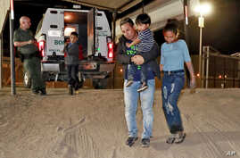 FILE - A Honduran man carries his 3-year-old son as his daughter and other son follow to a transport vehicle after being detained by U.S. Customs and Border Patrol agents in San Luis, Ariz., July 18, 2018. Border arrests figures for August 2018 are t