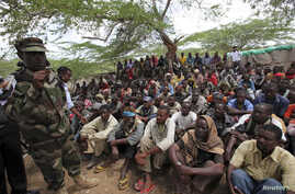 Members of al Qaida-linked militant group al Shabab listen to a Somalia government soldier after their surrender to the authorities in the north of Somalia's capital Mogadishu, September 24, 2012.