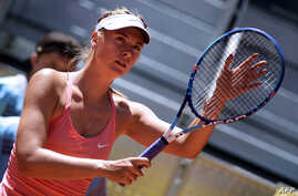 FILE - Russian tennis player Maria Sharapova touches her racket at the end of her match against Colombian Mariana Duque Marino in Madrid on May 5, 2015.