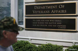 FILE - A man walks by the Department of Veteran Affairs building in Washington, May 23, 2014.