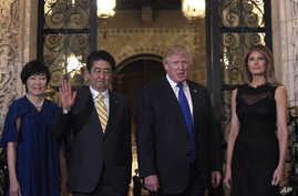 President Donald Trump, second from right, and first lady Melania Trump, right, stop to pose for a photo with Japanese Prime Minister Shinzo Abe, second from left, and his wife Akie Abe, left, before they have dinner at Mar-a-Lago in Palm Beach, Fla....