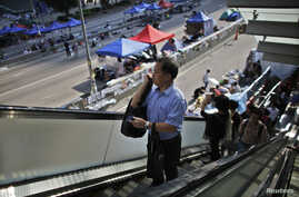 Government employees arrive to work as they walk along an area occupied by protesters outside of the government headquarters building in Hong Kong, Oct. 6, 2014.