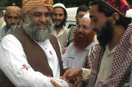 FILE - Maulana Fazl-ur-Rahman, left, leader of Pakistan's Jamiat Ulema-e-Islam party, is received by followers as he arrives in Pakistan at a border post near Lahore after a trip to India, July 24, 2003.