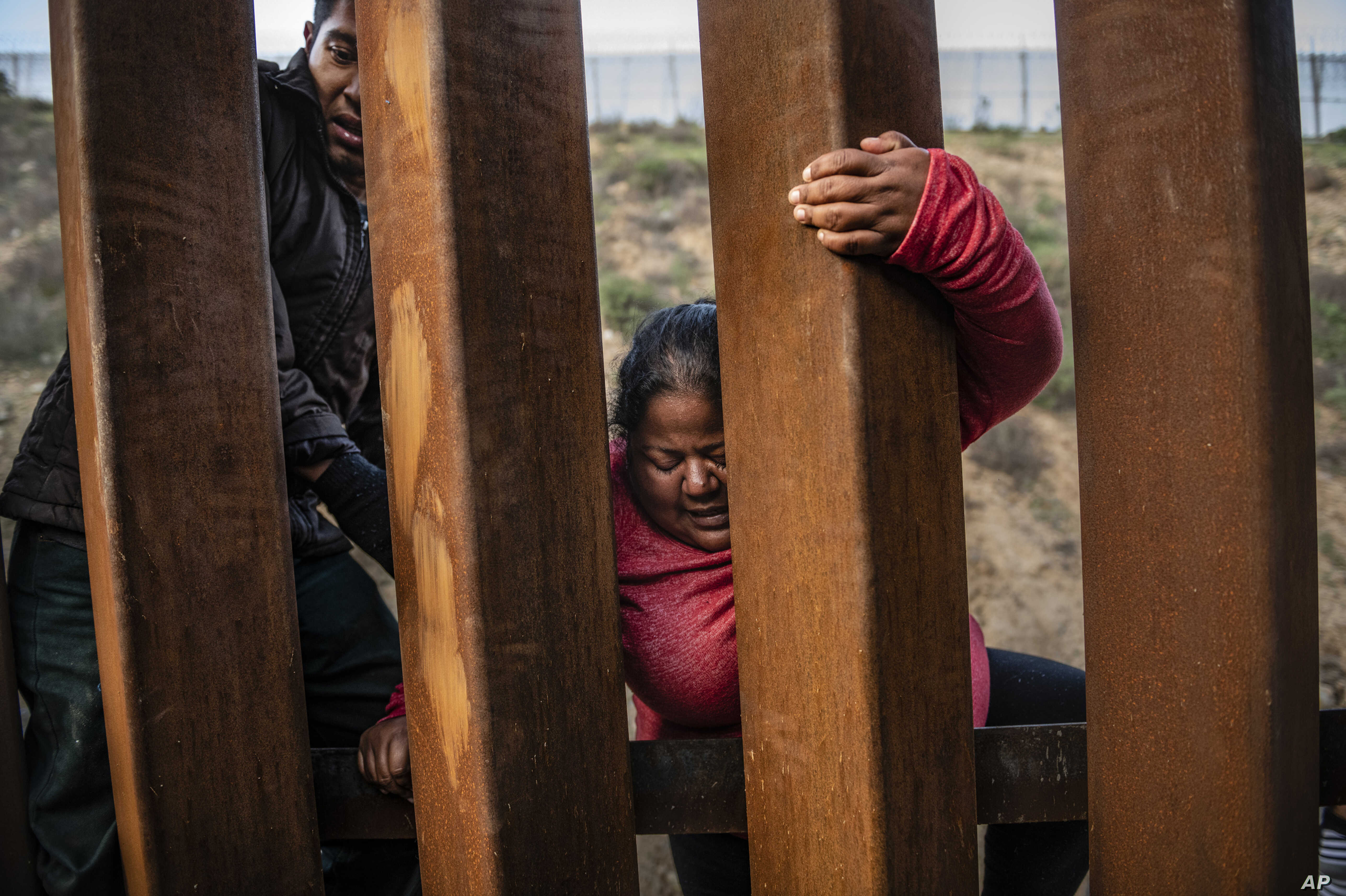 FILE - A migrant climbs the border fence before jumping into the U.S. in San Diego, California, from Tijuana, Mexico, Dec. 27, 2018.