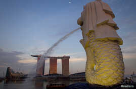FILE - The Merlion statue overlooking the Marina Bay area spouts water as the Marina Bay Sands resort and casino is pictured in the background.
