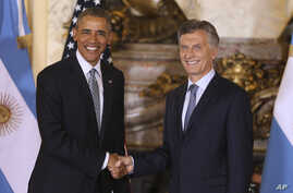 U.S. President Barack Obama shakes hands with Argentina's President Mauricio Macri at the government house in Buenos Aires, Argentina, March 23, 2016.