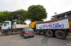 """Trucks form a blockade in Cayenne on March 26, 2017, with a banner reading """"Hollande (refering to French president Francois Hollande), where is your deal on the future ? No roads, no development""""."""