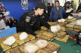 FILE - Thai policemen arrange packages of methamphetamine on a table before a press conference in Bangkok, Thailand, Feb. 15, 2013.