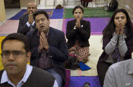 In this Jan. 17, 2016 photo, Ruma Roka, second from right, who runs an institute for young people with hearing impairment, joins a Buddhist chanting session in New Delhi, India. Chanting Buddhist mantras is catching on among India's urban elite as a