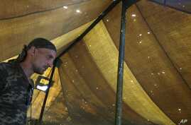 A Pro-Russian rebel stands in a tent riddled with holes caused by shrapnel at the Novoazovsk border crossing point,in eastern Ukraine, Friday, Aug. 29, 2014. In Novoazovsk, pro Russian rebel fighters looked to be in firm control, well-equipped and re