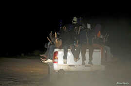 FILE - Migrants sit at the back of a truck as it is driven through a dust road at night in the desert town of Agadez, Niger, May 25, 2015.