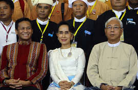 Myanmar's Foreign Minister Aung San Suu Kyi, center, sits with Myanmar's President Htin Kyaw, (Right), and Vice President Henry Van Hti Yu as they smile for a photo session following the Union Peace Conference-21st Century Panglong at the Myanmar Int