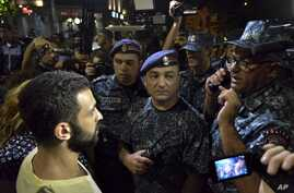Protesters speak to police officers during a night rally to support the radical opposition group gunmen in the Republican Square in Yerevan, Armenia on July 31, 2016.