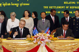 Australian Immigration Minister Scott Morrison, front left, signs a document together with Cambodian Interior Minister Sar Kheng, front right, during a signing ceremony of a controversial deal on resettlement of refugees inside the Interior Ministry
