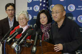 Family members watch as Kenneth Bae, right, freed during a top-secret mission, talks to reporters after he arrived at Joint Base Lewis-McChord, Washington, Nov. 8, 2014.