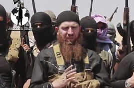 FILE -  Omar al-Shishani standing next to Islamic State of Iraq and the Levant (ISIL) spokesman among a group of fighters as they declare elimination of border between Iraq and Syria.