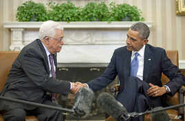 President Barack Obama (r) shakes hands with Palestinian President Mahmoud Abbas during their meeting in the Oval Office of the White House, March 17, 2014.