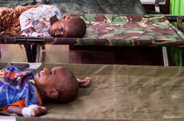Two sick children wait for treatment after being admited to a hospital in Agats, Asmat District, after the government dispatched military and medical personnel to the remote region of Papua to combat malnutrition and measles, Indonesia, Jan. 22, 2018