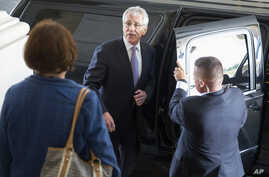 U.S. Defense Secretary Chuck Hagel (C) departs the U.S. Capitol after testifying at a closed Senate Armed Services hearing, July 8, 2014.