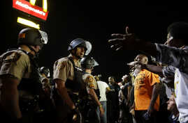 FILE - Officers and protesters face off along West Florissant Avenue in Ferguson, Mo., Aug. 10, 2015. The city released details Wednesday of a tentative deal with the U.S. Justice Department to reform its police department.