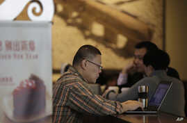FILE - A man surfs Internet on his laptop computer at a Starbucks cafe in Beijing, Feb. 16, 2015.