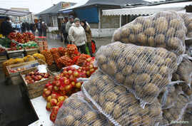 FILE - People walk past goods at the market in Suwalki, March 2009.