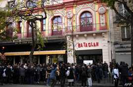 FILE - People stand in front of the Bataclan concert venue during ceremonies across Paris marking the second anniversary of the terror attacks of November 2015 in which 130 people were killed, in the French capital, Nov. 13, 2017.  Rapper Medine's sc