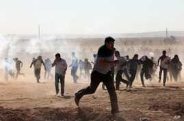 Turkish security forces use teargas and water cannons to disperse protesting local people as several hundred Syrian refugees wait at the border, in Suruc, Turkey, Sept. 21, 2014.