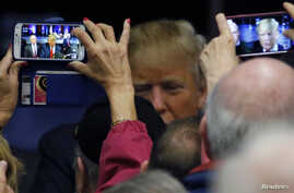 FILE - Suporters take pictures of U.S. Republican presidential candidate Donald Trump at rally in Bluffton, South Carolina, February 17, 2016.