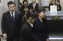 Ousted South Korean President Park Geun-hye, right, leaves after hearing on a prosecutors' request for her arrest for corruption at the Seoul Central District Court, March 30, 2017.
