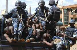 Rioters sit on the back of a police truck after their arrest in the capital city Kampala, Uganda, after riots broke out, April 29, 2011