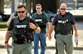 Officers arrive at the Orlando Police Headquarters during the investigation of a shooting at the Pulse nightclub, where people were killed by a gunman, in Orlando, Florida, June 12, 2016.