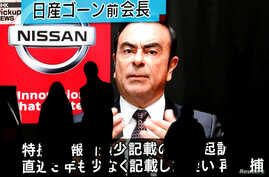 FILE - Passersby are silhouetted as a huge street monitor broadcasts news reporting ousted Nissan Motor chairman Carlos Ghosn's indictment and re-arrest in Tokyo, Japan, Dec. 10, 2018.