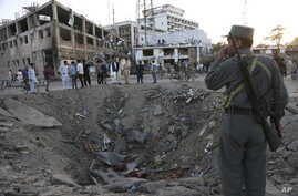 In this Wednesday, May 31, 2017 file photo, security forces stand next to a crater created by a massive explosion, that killed over 150 according to the Afghan president, in front of the German Embassy in Kabul.
