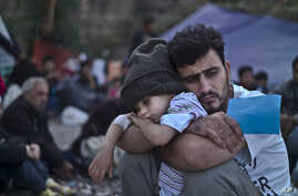 A Syrian refugee child sleeps on his father's arms while waiting at a resting point to board a bus, after arriving on a dinghy from the Turkish coast to the northeastern Greek island of Lesbos, Oct. 4 , 2015.