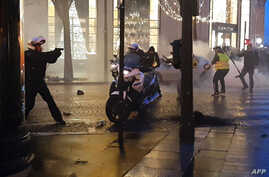 "This frame from a video taken Dec. 22, 2018, on the Champs-Elysees in Paris shows a police biker, left, drawing his firearm as he and other police bikers are assaulted by protesters, during the sixth consecutive Saturday of mobilization of the ""yello"