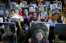 "Students hold portraits of deceased former South Korean ""comfort women"" during a weekly anti-Japan rally in front of the Japanese Embassy in Seoul, South Korea, Dec. 30, 2015."