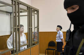 FILE - Jailed Ukrainian pilot Nadezhda Savchenko (L) stands in a defendant's cage during a court hearing in the town of Donetsk, Rostov-on-Don region, Russia, Sept. 29, 2015.