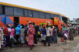 FILE - People board a commercial bus to flee following attacks by Boko haram in Bama and other parts of  Maiduguri, Nigeria, Sept. 8, 2014.