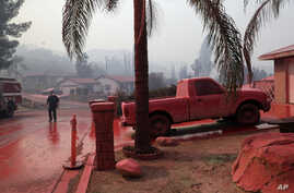 A truck and a street are covered in fire retardant dropped by an air tanker as crews battle a wildfire, Aug. 10, 2018, in Lake Elsinore, Calif.