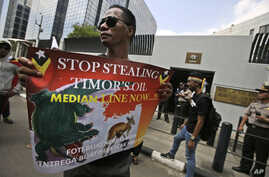 FILE - In this March 24, 2016 file photo, a protester holds a poster during a rally outside the Australian Embassy in Jakarta, Indonesia, as dozens of people show their support to East Timor in the dispute over oil and gas revenue-sharing between the