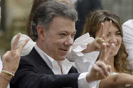 Colombia's President Juan Manuel Santos makes the victory sign after voting in a referendum to decide whether or not to support the peace deal he signed with rebels of the Revolutionary Armed Forces of Colombia, FARC, in Bogota, Colombia,  Oct. 2, 20