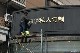 FILE - A worker removes part of a sign that consists of the Chinese characters that collectively read South Korea, at a shop in Shanghai, China, March 15, 2017