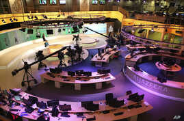 FILE - Staff members of Al-Jazeera International work at the news studio in Doha, Qatar, Jan. 1, 2015. Kuwait has given Qatar a list of demands from Saudi Arabia and other Arab nations that includes shutting down Al-Jazeera and cutting diplomatic ti