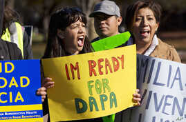 Danna Chavez Calvi, 23, (left) and a young woman who requested not to be named, participate in a rally for immigration reform after marching from Arlington, Va., to the White House in Washington, Nov. 20, 2015.