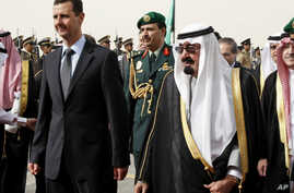 FILE - King Abdullah of Saudi Arabia, right, welcomes Syrian President Bashar Assad upon his arrival to attend the Arab Summit, in the Saudi capital Riyadh, March 11, 2009.