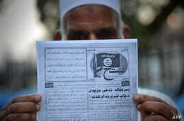 This photograph taken on September 3, 2014 shows a Pakistani man holding a pamphlet, allegedly distributed by the Islamic State (IS), in the northwestern Pakistani city of Peshawar.
