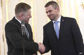 Outgoing Slovakian Prime Minister Robert Fico, left, shakes hands with  Peter Pellegrini, who will replace Fico as prime minister, at the Presidential palace in Bratislava, March 15, 2018.